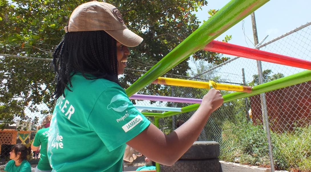 A volunteer paints playground equipment during her voluntary work overseas.